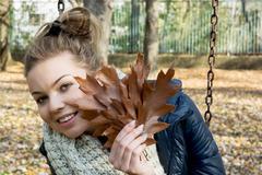 beautiful smiling teenage girl with brown oak leaves - stock photo