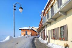 Narrow snowy street in small town. diano d'alba, italy. Stock Photos