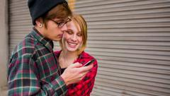 Hipster couple using smartphone and laughing Stock Footage