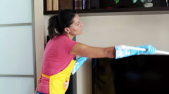 Woman dusting the tv and smiling to the camera Stock Footage