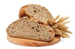 two halves a loaf of rye bread and wheat ears. - stock photo