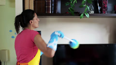 Woman dusting and answering the phone Stock Footage