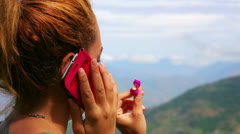Female tourist using mobile phone on top of mountain Stock Footage