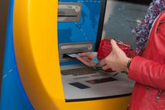 woman withdrawing cash at a bank atm - stock photo