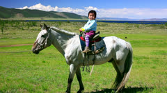 Young girl on horseback in Mongolian landscape Stock Footage