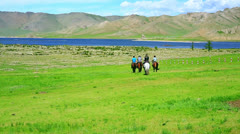 People riding horses in Mongolian landscape - stock footage