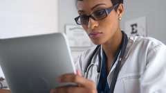 Doctor talking on smartphone and using tablet Stock Footage