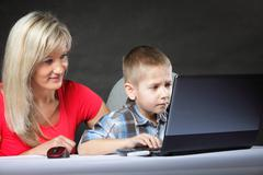 Stock Photo of mother with son looking on the laptop