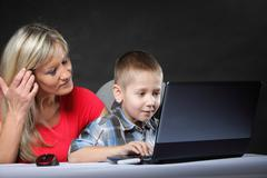 Mother with son looking on the laptop Stock Photos