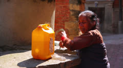 KATHMANDU, NEPAL - JUNE 2013: old woman pulling water containers from well Stock Footage