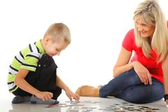 Stock Photo of mother playing puzzle together with her son