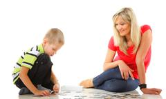 mother playing puzzle together with her son - stock photo