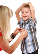 Mother fixing young boy's shirt Stock Photos