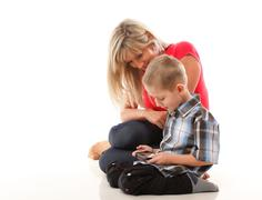 Mother and son playing video game on smart phone Stock Photos