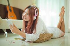 young asian woman listening to music - stock photo
