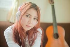 Young asian woman listening to music Stock Photos