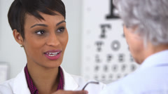 Black doctor puts on new glasses on old woman - stock footage