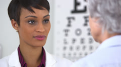 African doctor puts on new glasses on elderly woman - stock footage
