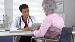 African American doctor taking notes while talking to old patient Stock Footage