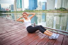 Woman exercising sit ups outside Stock Photos