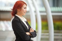 business woman smiling arms crossed - stock photo