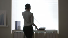 African American business woman talking on telephone in front of window Stock Footage