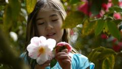Pretty Young Girl Picks And Smells A Flower, Gets Pollen On Her Nose Stock Footage