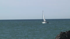 Sailboat Heads Out To Sea Horizon Ocean Blue Water Rocks Trip Journey Fun Stock Footage