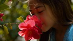 Adorable Little Girl Enjoys The Smell Of A Flower - stock footage