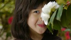 Adorable Little Girl Smells A Flower Stock Footage