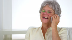 Old woman laughing on phone - stock footage