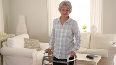 Old woman standing in room with walker Stock Footage