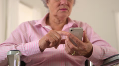 Old woman happily using smartphone - stock footage