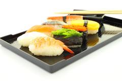 Sushi black rectangle plate focus shrimp on white table. Stock Photos
