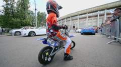 Boy in motorcyclist outfit sits on small bike during Speedfest Stock Footage