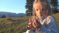 Child Playing with Cricket on Meadow in Mountains, Girl with Insect in Hand - stock footage