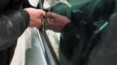 Stock Video Footage of Man in leather jacket tries to break door lock of car