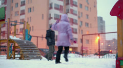 Two kids play on playground near dwelling house Stock Footage