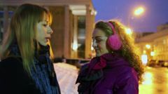 Two girls talk and gesture on street at winter evening Stock Footage