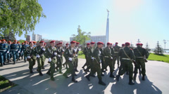 Soldiers in camouflage and red berets march Stock Footage