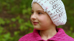 Young girl in white cap turns head and smiles, closeup Stock Footage