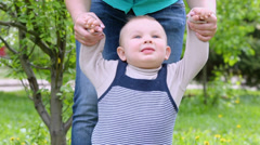 Mother holds her little son by hand and teaches him to walk Stock Footage