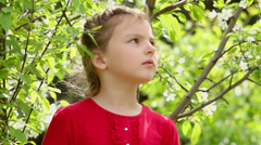 Young girl in dress stand near blooming tree and looks around Stock Footage