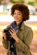 Autumn outdoor portrait of beautiful african american young woman holding a d Stock Photos