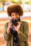 autumn outdoor portrait of beautiful african american young woman holding a d - stock photo