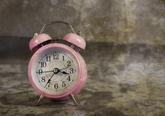 Retro pink alarm clock with vintage background Stock Photos