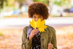 autumn outdoor portrait of beautiful african american young woman holding yel - stock photo