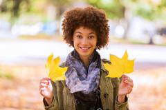 Autumn outdoor portrait of beautiful african american young woman holding yel Stock Photos