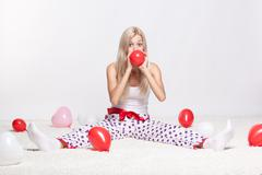 blonde woman inflating balloons - stock photo