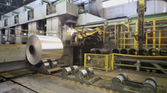 Worker oversees transporter which moves roll of aluminum - stock footage